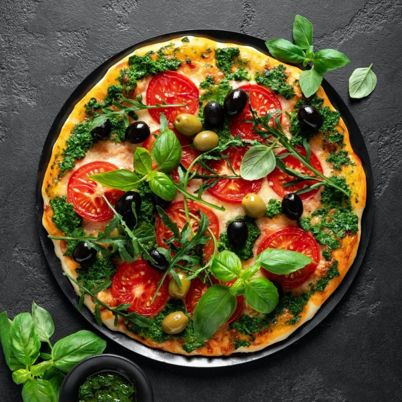 Pizza. Traditional italian pizza with green basil pesto sauce, top view